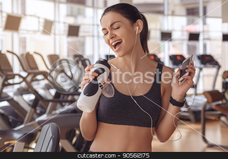 Young woman workout in gym healthy lifestyle stock photo, Young female training in gym healthy lifestyle listening music by Dmytro Sidelnikov