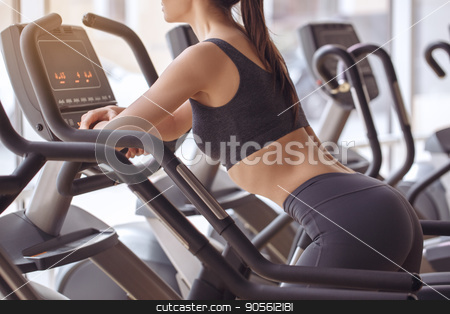 Young woman workout in gym healthy lifestyle stock photo, Young female training in gym healthy lifestyle elliptical trainer by Dmytro Sidelnikov