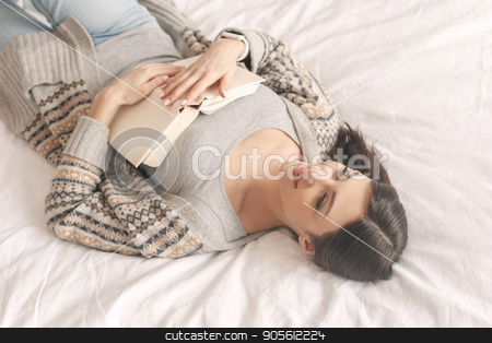 Young woman lie on bed with a book rest stock photo, Young girl lie on bed with a book relaxation dreaming by Dmytro Sidelnikov
