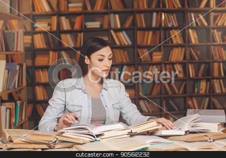 Young woman study in the library alone stock photo, Young female study in the library reading book by Dmytro Sidelnikov