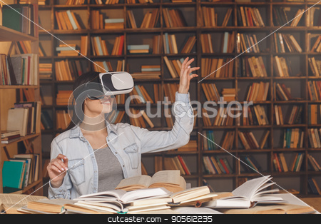 Young woman study in the library alone stock photo, Young female study in the library using virtual reality headset by Dmytro Sidelnikov