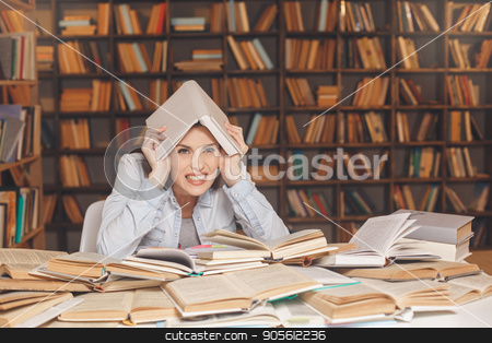 Young woman study in the library alone stock photo, Young female study in the library upset by Dmytro Sidelnikov
