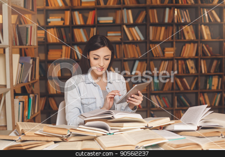Young woman study in the library alone stock photo, Young female study in the library browsing tablet by Dmytro Sidelnikov
