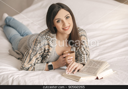 Young woman lie on bed with a book rest stock photo, Young girl lie on bed reading a book drinking tea by Dmytro Sidelnikov