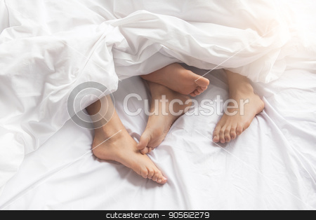 Young couple intimate relationship on bed passion stock photo, Young couple man and woman intimate relationship on bed feet by Dmytro Sidelnikov