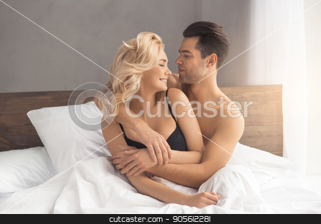 Young couple intimate relationship on bed passion stock photo, Young couple man and woman intimate relationship on bed hugging by Dmytro Sidelnikov