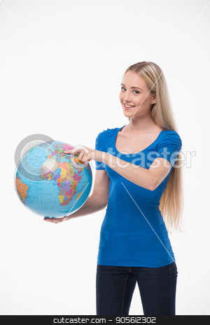 Beautiful young woman on white background stock photo, Travel concept. Portrait of stylish beautiful young woman isolated on white background. Woman smiling, pointing at globe by Dmytro Sidelnikov