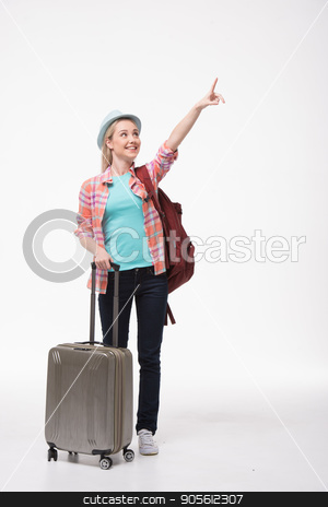 Beautiful young woman on white background stock photo, Travel concept. Portrait of stylish beautiful young woman isolated on white background. Woman with suitcase and backpack smiling and pointing up by Dmytro Sidelnikov