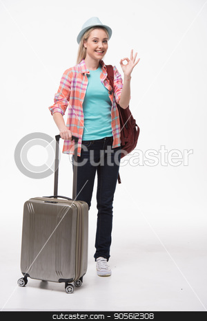 Beautiful young woman on white background stock photo, Travel concept. Portrait of stylish beautiful young woman isolated on white background. Woman with suitcase and backpack smiling and showing ok sign by Dmytro Sidelnikov