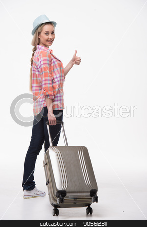 Beautiful young woman on white background stock photo, Travel concept. Back view photo of stylish beautiful young woman isolated on white background. Woman with suitcase smiling and showing thumb up by Dmytro Sidelnikov