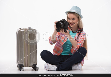 Beautiful young woman on white background stock photo, Travel concept. Portrait of stylish beautiful young woman isolated on white background. Woman smiling, sitting near suicase and using camera by Dmytro Sidelnikov