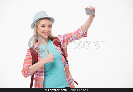 Beautiful young woman on white background stock photo, Travel concept. Portrait of stylish beautiful young woman isolated on white background. Woman with backpack smiling and making selfie on mobile phone by Dmytro Sidelnikov