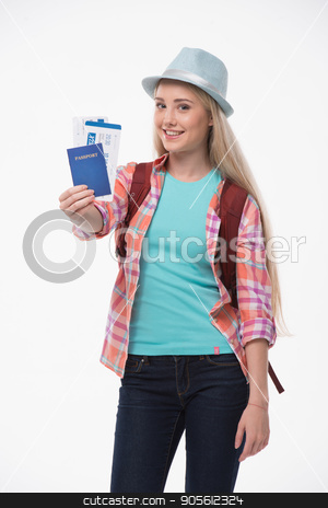 Beautiful young woman on white background stock photo, Travel concept. Portrait of stylish beautiful young woman isolated on white background. Woman with backpack smiling, looking at camera and showing passport with tickets by Dmytro Sidelnikov