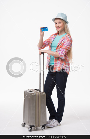 Beautiful young woman on white background stock photo, Travel concept. Portrait of stylish beautiful young woman isolated on white background. Woman with suitcase smiling, looking at camera and showing credit card by Dmytro Sidelnikov
