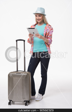 Beautiful young woman on white background stock photo, Travel concept. Portrait of stylish beautiful young woman isolated on white background. Woman with suitcase smiling and using tablet computer by Dmytro Sidelnikov