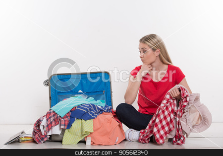 Beautiful young woman on white background stock photo, Travel concept. Portrait of stylish beautiful young woman isolated on white background. Woman sitting near suicase full of clothes by Dmytro Sidelnikov