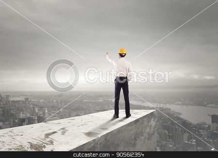 Businessman with helmet indicates the right direction stock photo, Businessman with helmet indicates the right direction on the roof above the city by Federico Caputo