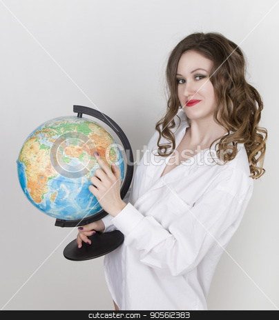 Young beautiful woman in white mens shirt with globe stock photo, Young beautiful woman in white mens shirt with globe. by Alexander