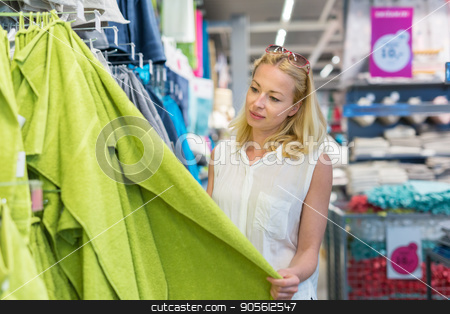 Woman choosing the right towel for her apartment in a modern home furnishings store. stock photo, Pretty, young woman choosing the right towel for her apartment in a modern home decor furnishings store. by kasto