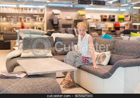 Woman shopping for furniture, sofa and home decor in store stock photo, Caucasian woman shopping for furniture, sofa and home decor in store. Lady sitting on couch imagining her new home architectural arrangement. by kasto