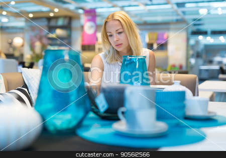 Woman choosing the right decor for her apartment in a modern home furnishings store. stock photo, Pretty, young woman choosing the right item for her apartment in a modern home decoration furnishings store. by kasto