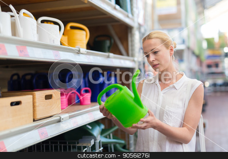 Woman choosing the right item for her apartment in a modern home furnishings store. stock photo, Beautiful young caucasian woman choosing the right item for her apartment in a modern home decor furnishings store. Shopping in retail store. by kasto