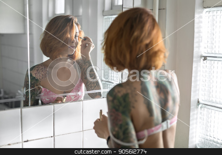 Tattooed girl does makeup stock photo, Concentrated girl with colorful tattoos applying mascara on her eyelashes while standing opposite the mirror in the bathroom with white tiled walls. She wears a rose lingerie. Indoors. Horizontal by bezikus