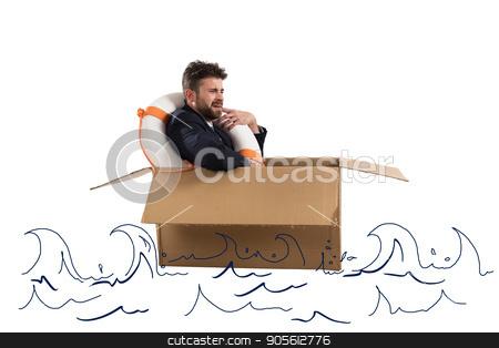Afraid businessman with cardboard in the ocean stock photo, Afraid businessman with cardboard and lifebelt in the ocean by Federico Caputo