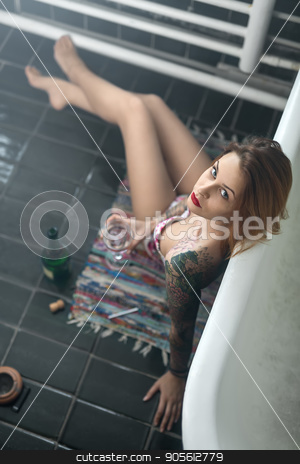 Tattooed girl posing in bathroom stock photo, Sexy girl with colorful tattoos leans on the bath while sits with crossed legs on the motley carpet on the dark tiled floor in the bathroom. She holds a glass and looks into the camera. Indoors by bezikus