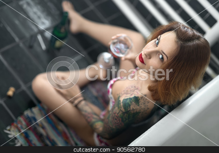 Beautiful girl with colorful tattoos sits near white bath on the stock photo, Beautiful girl with colorful tattoos sits near white bath on the motley carpet on the dark tiled floor in the bathroom. She holds a glass and looks into the camera. Top view photo. Indoors by bezikus