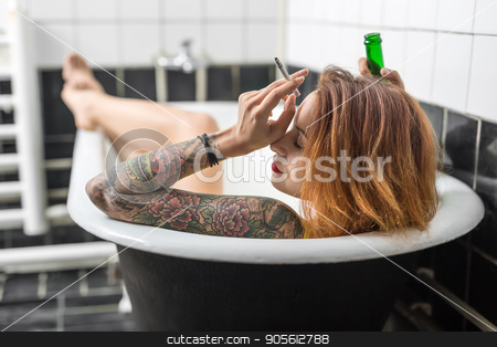 Tattooed girl relaxing in bath stock photo, Naughty girl with closed eyes and colorful tattoo on the arm lies in the bath in the bathroom with black and white tiles. She holds a cigarette and a green bottle in her hands. Indoors. Horizontal by bezikus