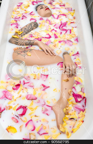 Charming girl with fancy tattoos lies in the white bath full of stock photo, Charming girl with fancy tattoos lies in the white bath full of water with milk and colorful flower petals. Her eyes are closed. Top view photo. Indoors. Vertical by bezikus