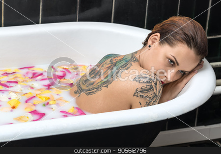 Tattooed girl relaxing in bath stock photo, Nude girl with wet hair lies in the white bath full of water with milk and flower petals. She has a colorful fox tattoo on the back and another tattoo on the shoulder. Beauty holds head on her hands by bezikus