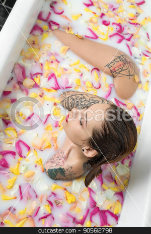 Delightful girl with wet hair and colorful tattoos sits in the w stock photo, Delightful girl with wet hair and colorful tattoos sits in the white bath full of water with milk and flower petals. Her eyes are closed. Top view photo. Indoors. Vertical by bezikus