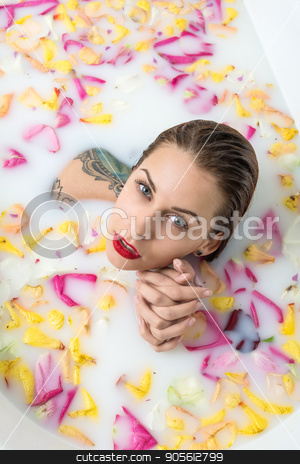 Tattooed girl relaxing in bath stock photo, Charming girl with wet hair and colorful tattoos in the white bath full of water with milk and flower petals. Beauty holds her hands together and looks into camera with parted lips. Top view photo by bezikus