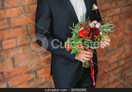 elegant man dressed in a modern black suit and white shirt holding in hand a wedding flowers bouquet from red carnation. Close up color vertical image of male hands holding bunch of bright flowers. stock photo, the elegant man dressed in a modern black suit and white shirt holding in hand a wedding flowers bouquet from red carnation on a brick wall background. date, engagement, romantic, event concept. by Dmitry