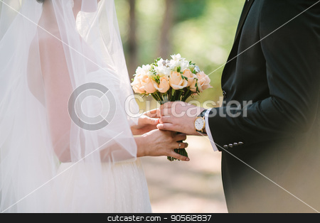 the groom gives to the bride a wedding bouquet outdoor. stock photo, the groom in a black suit gives to the bride in white dress with veil a wedding bouquet outdoor. date, engagement, romantic, love, feeling, event concept. wedding ceremony. by Dmitry