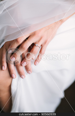Bride's morning. young beautiful bride in white wedding dress gracefully put hand together. french nail concept. stock photo, Bride's morning. young beautiful bride in white wedding dress and veil puting hand together on a knee. engagement ring with big diamond. wedding nail concept. by Dmitry