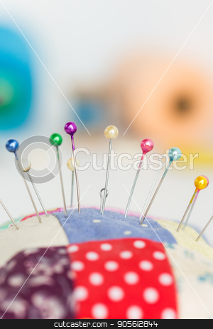 closeup sewing tools, patchwork, tailoring and fashion concept - macro with colorful stitched pincushion and many beautiful pins, background skeins of pink and blue thread, selective focus, vertical. stock photo, closeup sewing tools, patchwork, tailoring and fashion concept - macro with colorful stitched pincushion and many beautiful pins, background skeins of pink and blue thread, selective focus, vertical by Dmitry