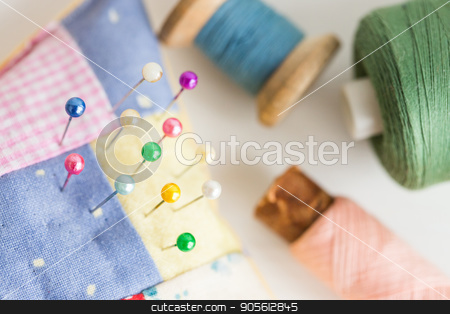 needlework, craft, sewing and tailoring concept - macro with beautiful stitched pincushion and colorful pins, pink, blue and green thread spools, white background, selective focus. stock photo, needlework, craft, sewing and tailoring concept - macro with beautiful stitched pincushion and colorful pins, pink, blue and green thread spools, white background, selective focus by Dmitry