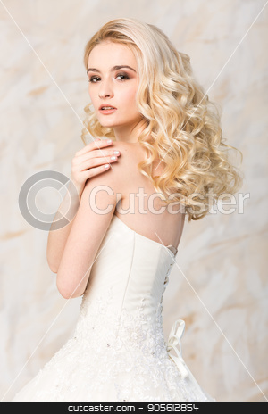 fashionable gown, beautiful blonde model, bride hairstyle and makeup concept - young romantic lady in white wedding dress, slender woman stand indoors on light background, side view on hands and back. stock photo, fashionable gown, beautiful blonde model, bride hairstyle and makeup concept - young romantic lady in white wedding dress, slender woman stand indoors on light background, side view on hands and back by Dmitry