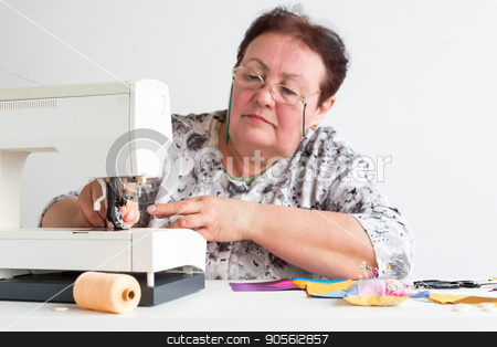 patchwork and quilting at the workshop of a tailor woman on white background - older woman with glasses is preparing to work on the sewing machine with scraps of colored fabrics. stock photo, patchwork and quilting at the workshop of a tailor woman on white background - older woman with glasses is preparing to work on the sewing machine with scraps of colored fabrics by Dmitry