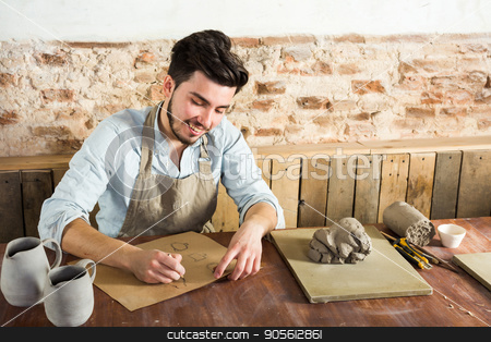 potter, workshop, artisan tools, ceramics art concept - smiling young male man working on the design of future products, a ceramist sitting behind desk with tools, fireclay and finished jugs. stock photo, potter, workshop, artisan tools, ceramics art concept - smiling young male man working on the design of future products, a ceramist sitting behind desk with tools, fireclay and finished jugs by Dmitry
