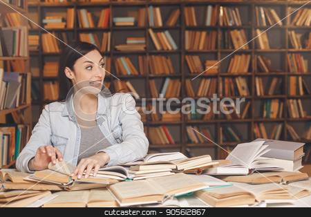 Young woman study in the library alone stock photo, Young female study in the library grimase by Dmytro Sidelnikov