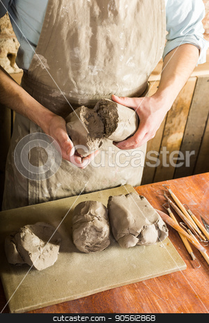 potter, clay, ceramics art concept - top view on hands of young master holding pieces of fireclay, male dressed in an apron, a ceramist with raw materials on table with sculpting tools set. stock photo, potter, clay, ceramics art concept - top view on hands of young master holding the large pieces of fireclay, male dressed in an apron, a ceramist with raw materials on table with sculpting tools set. by Dmitry