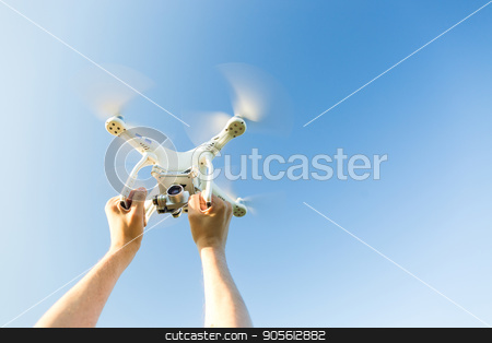 quadcopter outdoors, aerial imagery and recreation concept - closeup on human hands grip on frame of white quadrocopter flying on background of blue cloudless sky, male man caught flying drone. stock photo, quadcopter outdoors, aerial imagery and recreation concept - closeup on human hands grip on frame of white quadrocopter flying on background of blue cloudless sky, male man caught flying drone by Dmitry