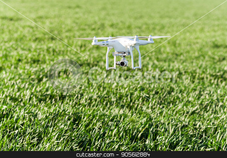quadcopter outdoors, aerial imagery and recreation concept - low flying white drone with four propellers and build-in digital camera at background of summer grass field, quadrocopter on takeoff. stock photo, quadcopter outdoors, aerial imagery and recreation concept - low flying white drone with four propellers and build-in digital camera at background of summer grass field, quadrocopter on takeoff by Dmitry