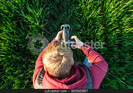 fascinating photography and process of shooting concept - top view of young male man with mirror camera in hands standing in a field of bright green grass, jeans and jacket hoodie. stock photo, fascinating photography and process of shooting concept - top view of young male man with mirror camera in hands standing in a field of bright green grass, jeans and jacket hoodie by Dmitry