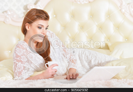 young woman with laptop stock photo, Beautiful young woman on bed with laptop by Ruslan Huzau