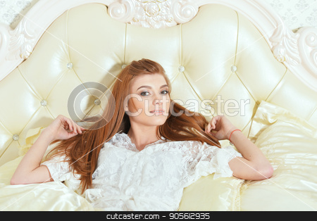 beautiful young woman stock photo, beautiful young woman in white blouse posing on vintage bed by Ruslan Huzau